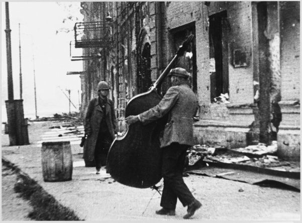 A civilian salvages a double- bass from the ruins of his home