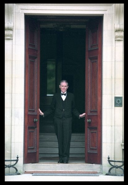 A rather dour butler opens the doors of an Edwardian mansion