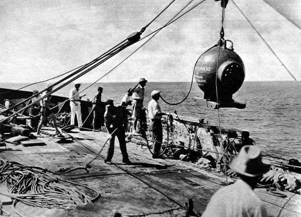 Photograph of Dr. William Beebe's bathysphere being lowered into the sea off St