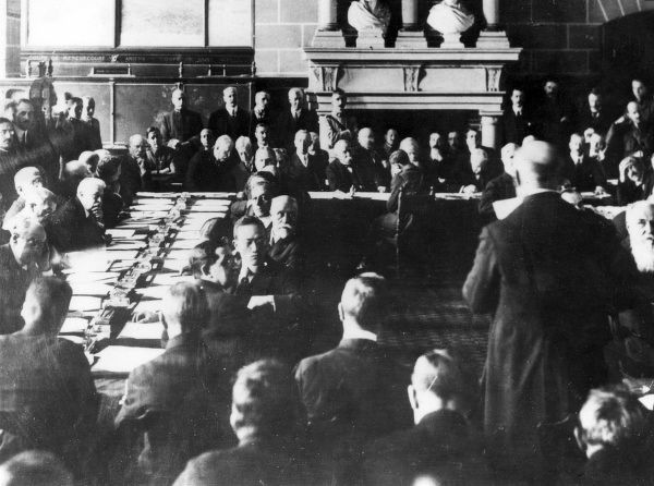 Dr Karl Renner (1870-1950), Austrian politician, at a Peace Conference in St Germain Chateau, France, seen here standing, with his back to the camera, replying to the Allied delegates after receiving the terms of the St Germain en Laye Peace Treaty