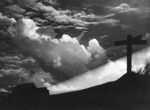 A dramatic cloud formation below some road signs, looking almost like a crucifixion scene. Date: 1940s