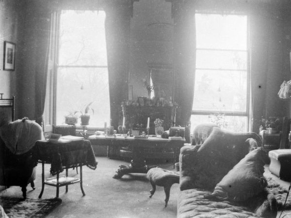 The typically Victorian drawing room of a country house, somewhere in South Wales. There are two large sash windows with a mirror in between, reflecting a ceiling rose. There is a chaise longue on the right, with an upholstered chair just behind it