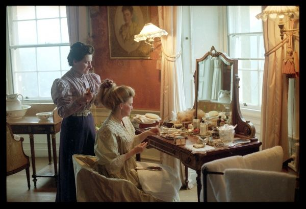 Lady Anna Olliff-Cooper sits at her dressing table while Eva Morrison, the Lady's Maid, puts her hair up for her