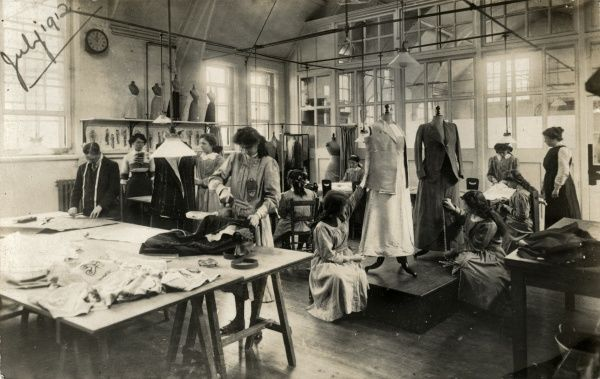 Staff in the workroom of a dressmaker or outfitter. Clothes in various stages of completion are on dummies. The employees (all female apart from a solitary man with a tape measure around his neck) measure, mark, cut, sew and iron