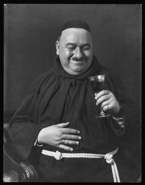 A portly monk with a moustache smiles to himself as he prepares to drink a glass of wine or a similar tipple