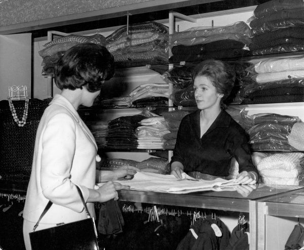 A young woman leaves a garment with a helpful shop assistant with a bouffant hairdo, behind the counter of a dry cleaning shop. Date: 1960s