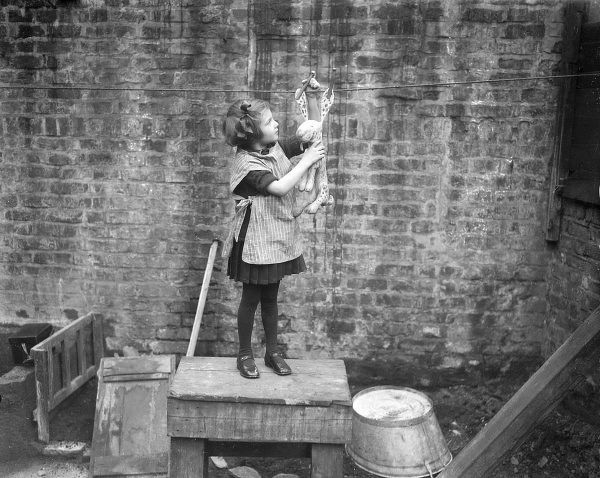 A little girl pegs out her freshly washed 'Dismal Desmond' toy dalmatian dog to dry on the washing line in her back yard! Date: early 1930s