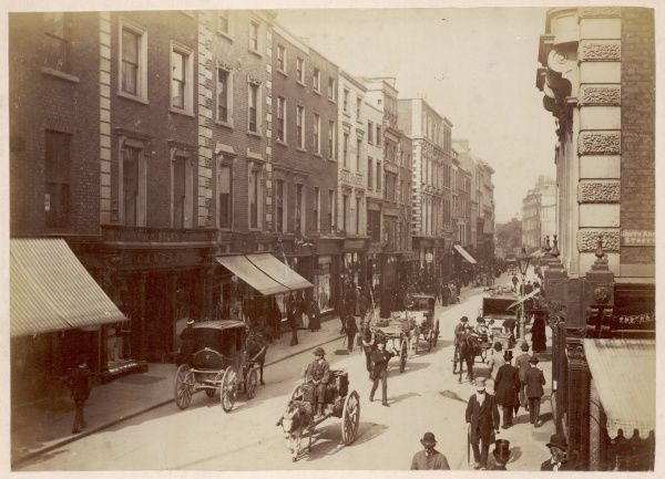 a lively street scene in central Dublin with a variety of horse-drawn transport and a donkey cart, delivering goods