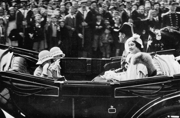 The Duke of York, in the uniform of a Rear-Admiral, and his wife the Duchess pass Trafalgar Square in an open Landau. Facing them are Princess Elizabeth and Princess Margaret. 1935