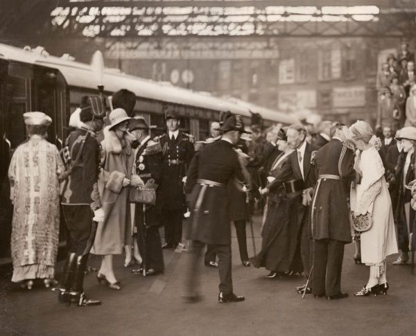 The Duke and Duchess of York (later King George VI and Queen Elizabeth) arrive home by train to Victoria Station and are greeted by family members. The Duke of York can be seen in uniform on the right, greeting Princess Mary