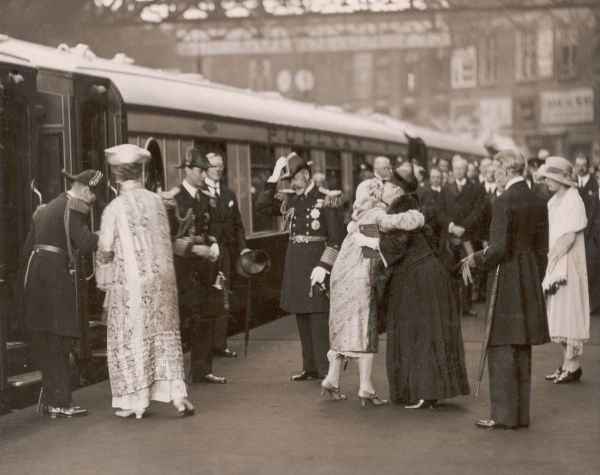 The Duke and Duchess of York (later King George VI and Queen Elizabeth) arrive home by train to Victoria Station and are greeted by family members, including King George V and Queen Mary. The Duchess of York can be seen greeting her mother