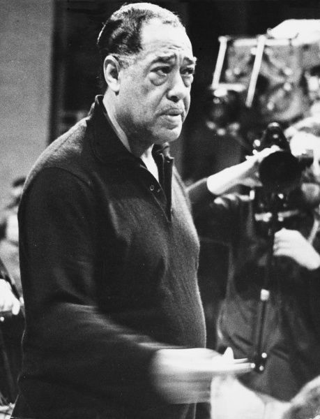 DUKE ELLINGTON (Edward Kennedy Ellington) American bandleader and jazz composer, looking rather hounded by Press photographers. Date: 1899 - 1974