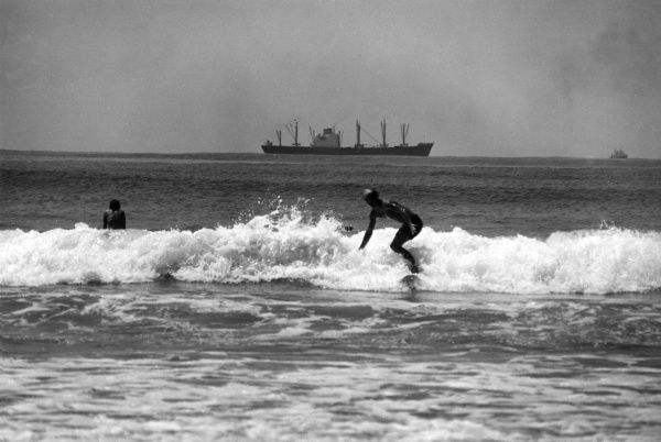 Surfing at Durban, South Africa. Date: late 1960s