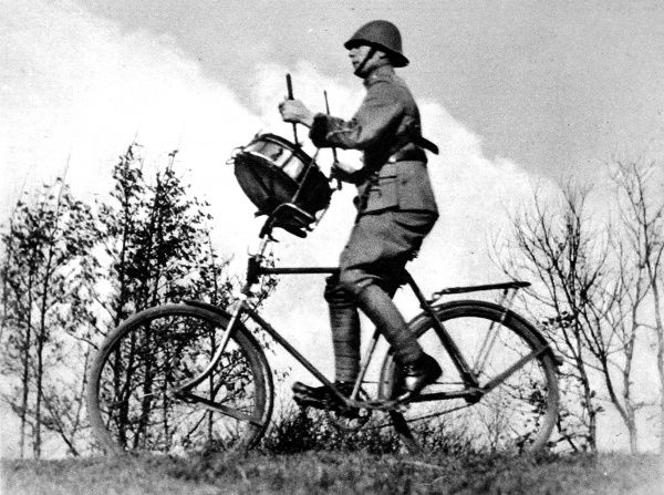 Photograph showing a Dutch army drummer of the Bicycle-Mounted Regiment; stationed at S'Hertogenbosch, September 1937. The drummer was provided with an arm-rest in order to improve his steering