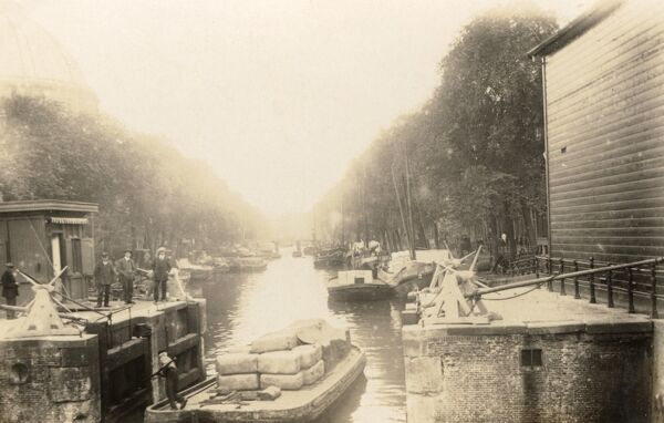 Dutch Canal scene with barges and a group of three canal officials (left). A barge operative poles is vessel trough the opened lock gate. Date: 1910s