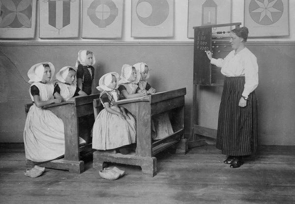 A group of Dutch schoolgirls in traditional hats, dresses and clogs, sitting at their desks at a school in Arnemuiden, Middleburg, the Netherlands. Date: early 1930s