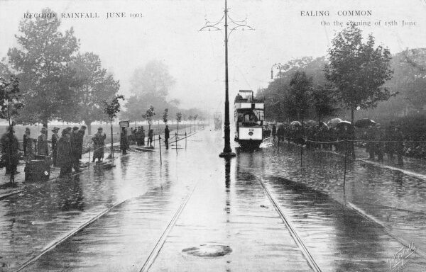The record rainway of June 1901 - view of some rather soggy pedestrians and a struggling open-top (!) tram at Ealing Common, Ealing, London on the evening of the 15th June