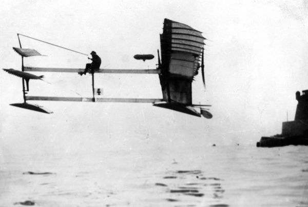 A rather precarious-looking aeroplane, flying very low over the sea. Date: early 1900s