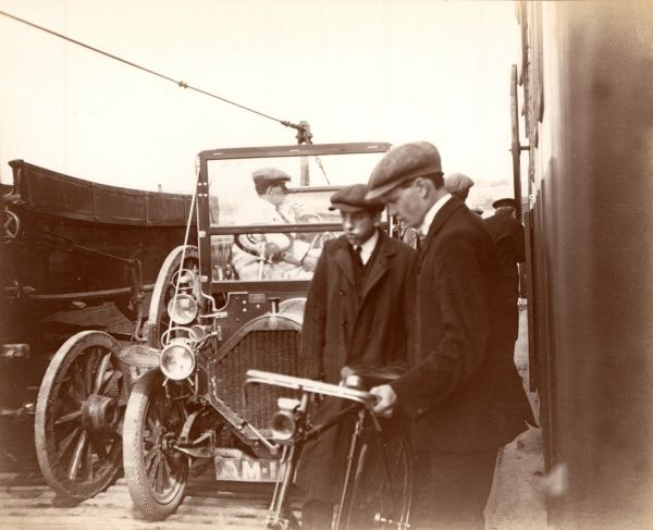 An early convertible car on a car ferry alongsode a large cart/wagon and a couple of lads with a bicycle