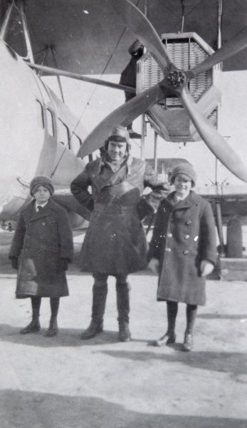 A pilot stands with two children in front of an aircraft taking them on a London to Paris flight, in the early days of aviation