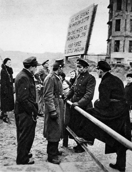 Photograph showing a West Berlin policeman (on left) talking to a Soviet Sector policeman over an East-West frontier barrier, in Berlin, 1949