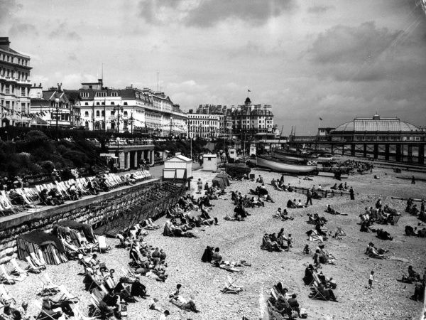 The beach and promenade at Eastbourne, Sussex, England, looking very packed, at the height of the summer season. Date: 1950s