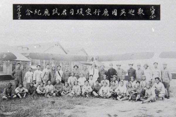 A large group of Eastern aviators in the Far East, posing for their photo in a field, in front of an aeroplane