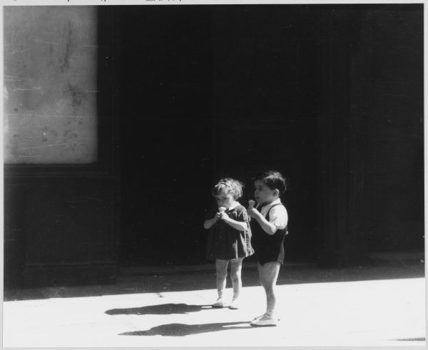 Two young children stand outside eating ice-creams