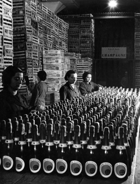 Sober women sorting bottles of Edecan Champagne, Mexico, South America. Date: 1930s