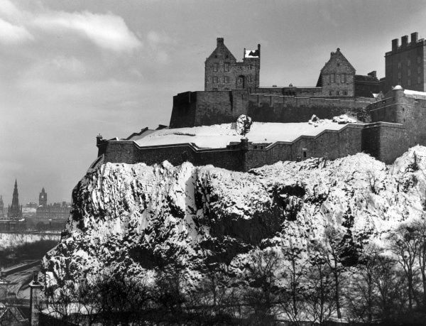 A striking view of Edinburgh Castle, Scotland, with its steep rocks mantled in snow. View from Castle Terrace. Date: 1960s
