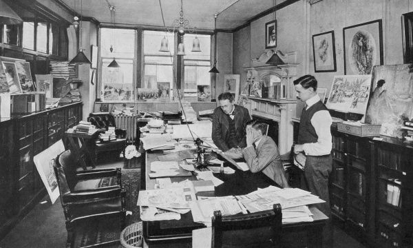 A photograph showing the editor's office of the Illustrated London News with editor Bruce Ingram, seated, assessing a a drawing submitted for publication by one of the ILN special artists