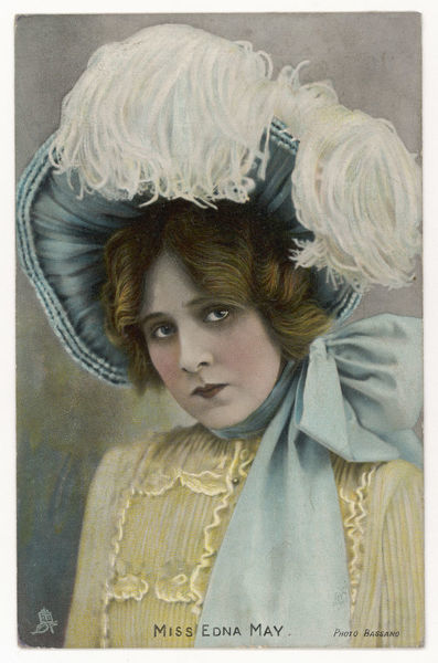 Edna May in a bonnet style hat tied with a large bow under the chin & worn tilted upwards to reveal the underside of the brim. White ostrich plumes complete the effect