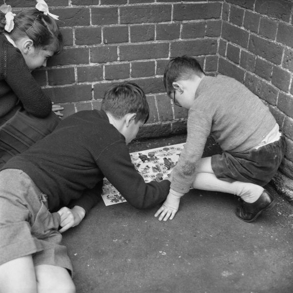 Two schoolboys crouch to play a board game in the corner of the playground, watched by a small girl