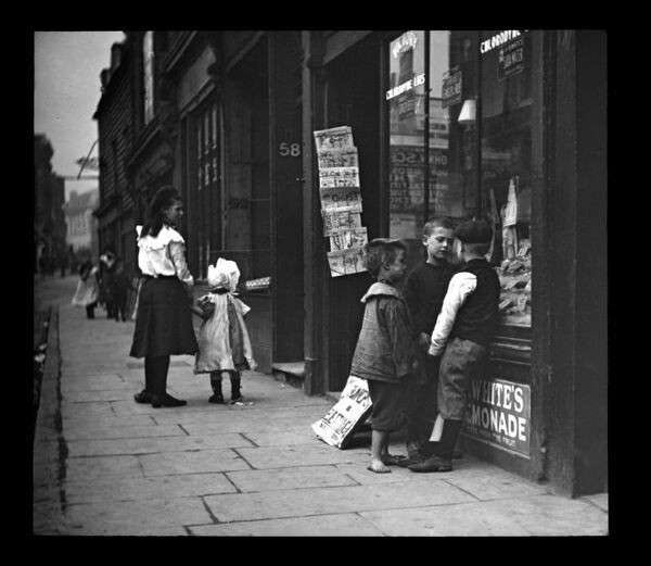 A group of Edwardian children outside a shop -- one of the boys has bare feet