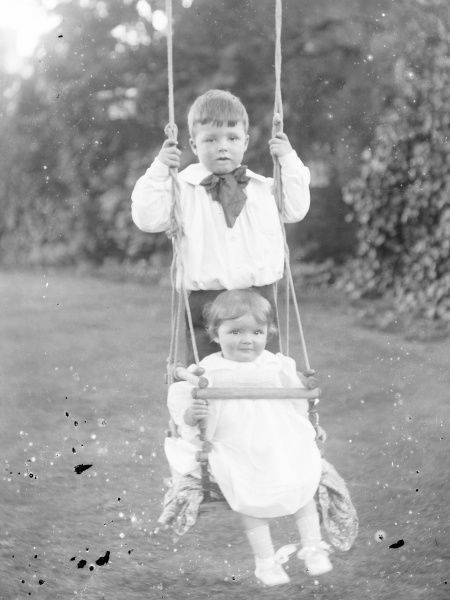 Two Edwardian children on a swing in a garden, Mid Wales. The swing has a safety bar at the front