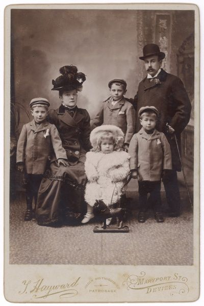 An Edwardian family of six pose for their photo in the photographer's studio. The three boys are dressed in identical jackets and caps. The little girl has a toy horse on wheels