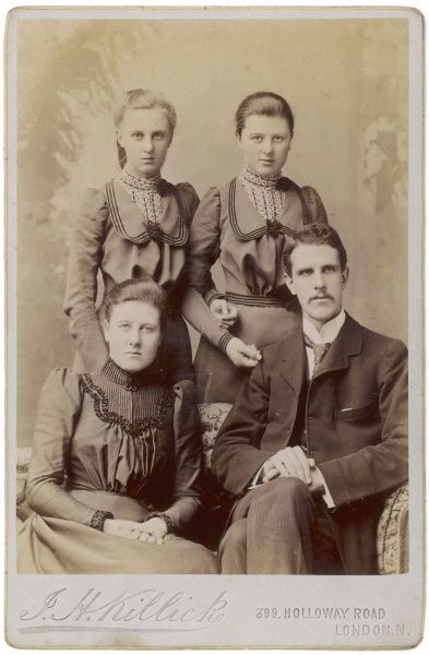 An Edwardian family of four pose for their photo in the photographer's studio. Mother and father are seated, and their two daughters stand behind them in identical dresses