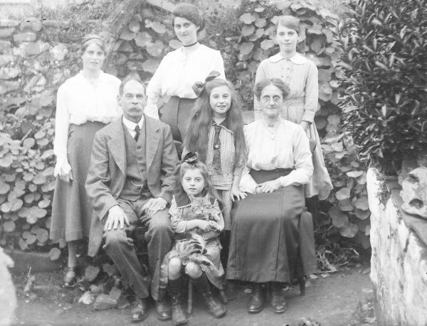 A middle class Edwardian family pose for a group photograph in a garden, probably in the Mid Wales area. The little girl in the middle is holding a tabby cat in her arms