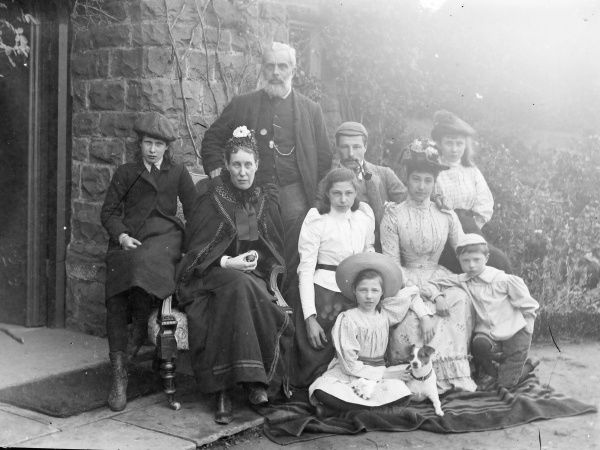 A large, middle class Edwardian family (adults,children and dog) pose for a group photograph outside their house, probably in the Mid Wales area. Date: early 20th century