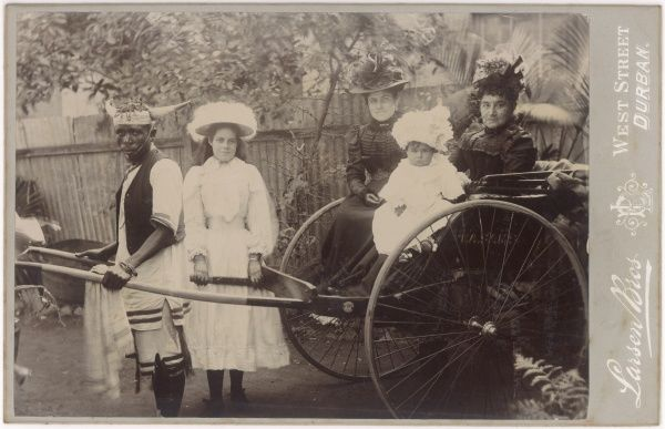An Edwardian family in South Africa. Two women sit in an open carriage with a baby, while a girl and a native man hold the shafts at the front