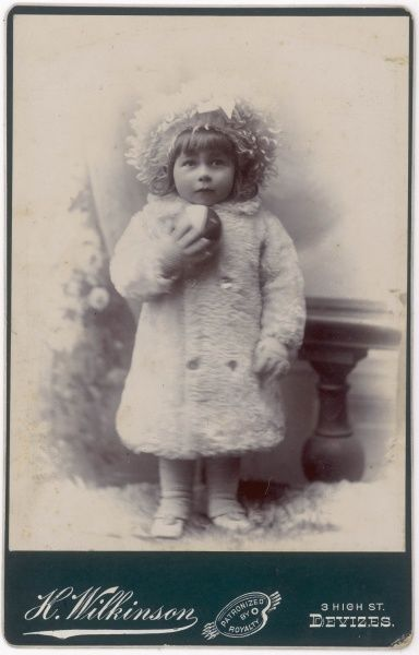 A little Edwardian girl in a white fur coat and hat, holding a ball. She is posing in the photographer's studio