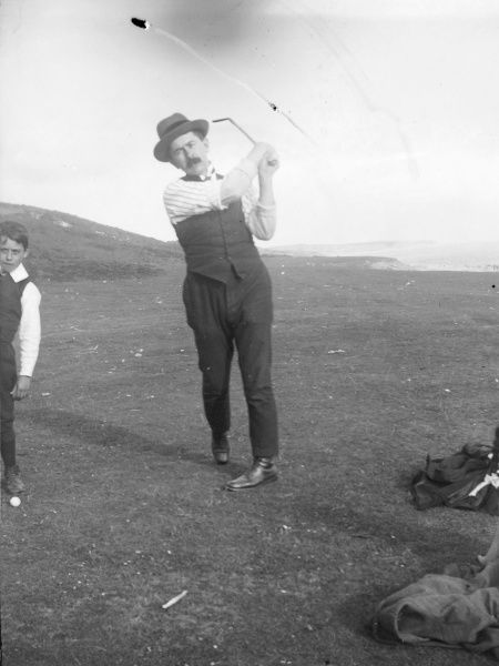 An Edwardian golfer in action in his shirtsleeves on the Pembrokeshire coast, South Wales