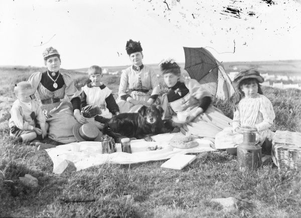 An Edwardian group (three women, three children and a dog) enjoying a picnic in a field. The cloth is set out with a teapot, a jampot, some scones, and a large loaf of bread. A large milk churn and a basket can be seen on the right