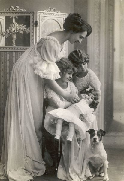 A Edwardian mother and her two little girls and their doll and dog pose in front of a screen