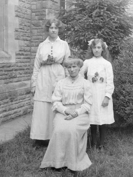 Three middle class Edwardian women, from three generations of one family, pose for a photograph in a garden, probably in the Mid Wales area