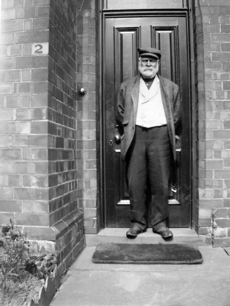 A middle-aged Edwardian workman, standing on the front doorstep of his newly built house, somewhere in Pembrokeshire, South Wales. He is wearing a slightly shabby looking suit, with a smart white waistcoat and a flat cap