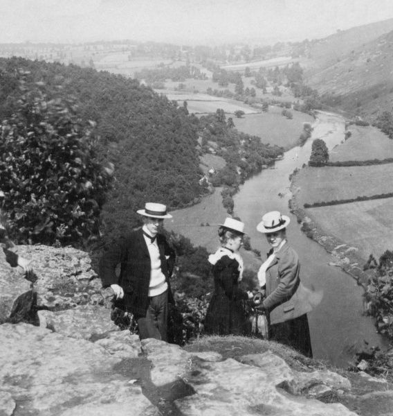 Three Edwardians, a man and two women, enjoying a walk in the English countryside. A river winds its way through the landscape in the background