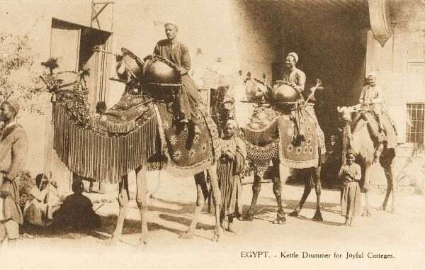 Two kettle drum players - their drums mounted onto the flanks of camels. They are ceremonial players, providing music for traditional social or religious corteges, parades or processions