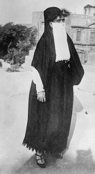 A mohammedan muslim woman with her face covered, probably in Egypt or another North African country. Date: 1930s