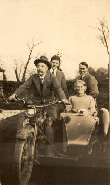 A elderly man sits on a muddy looking motorbike while his wife smiles from the attached sidecar. Two men, possibly their sons, grin in the background